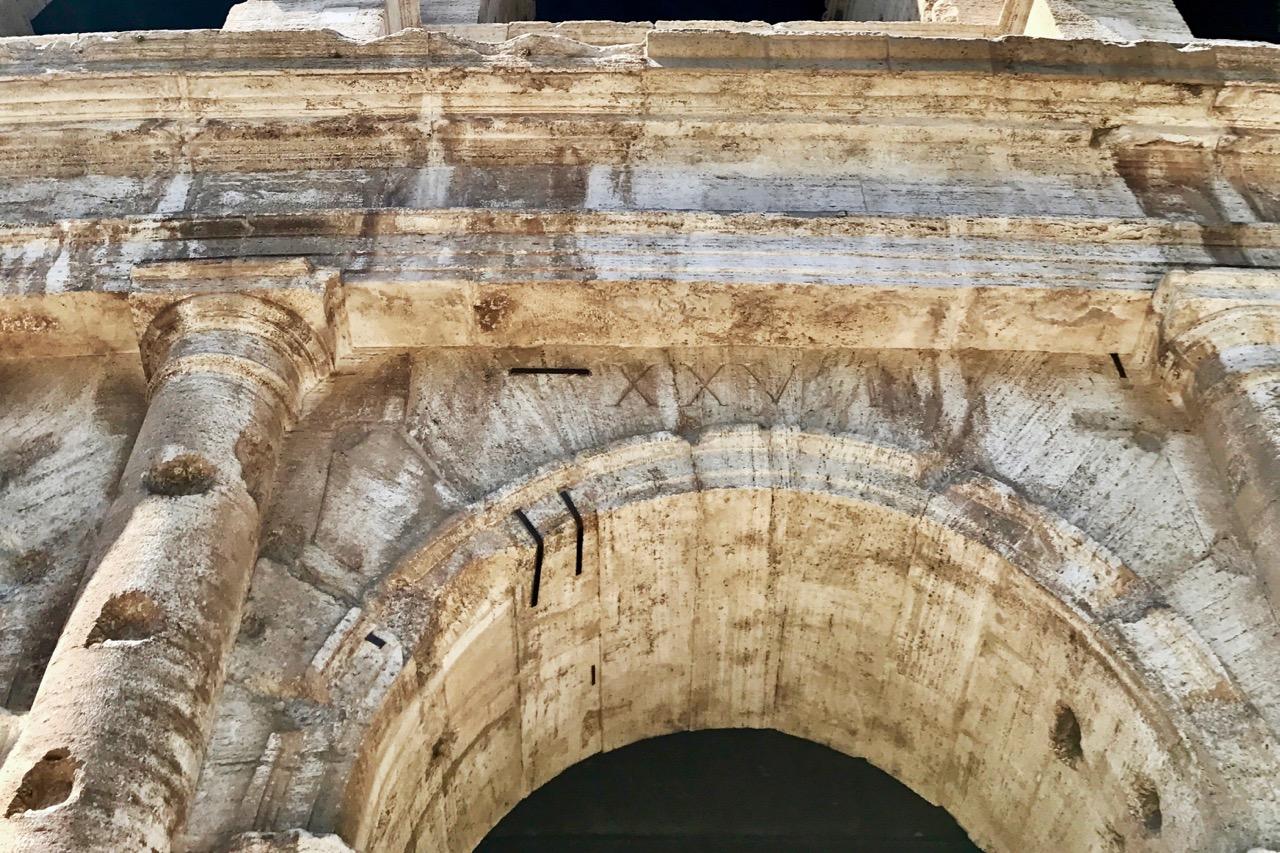 closeup of original number over entrance to rome colosseum