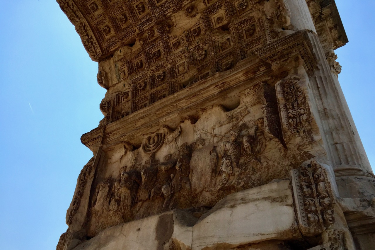 arch of titus depicting romans bringing back spoils of war from judea