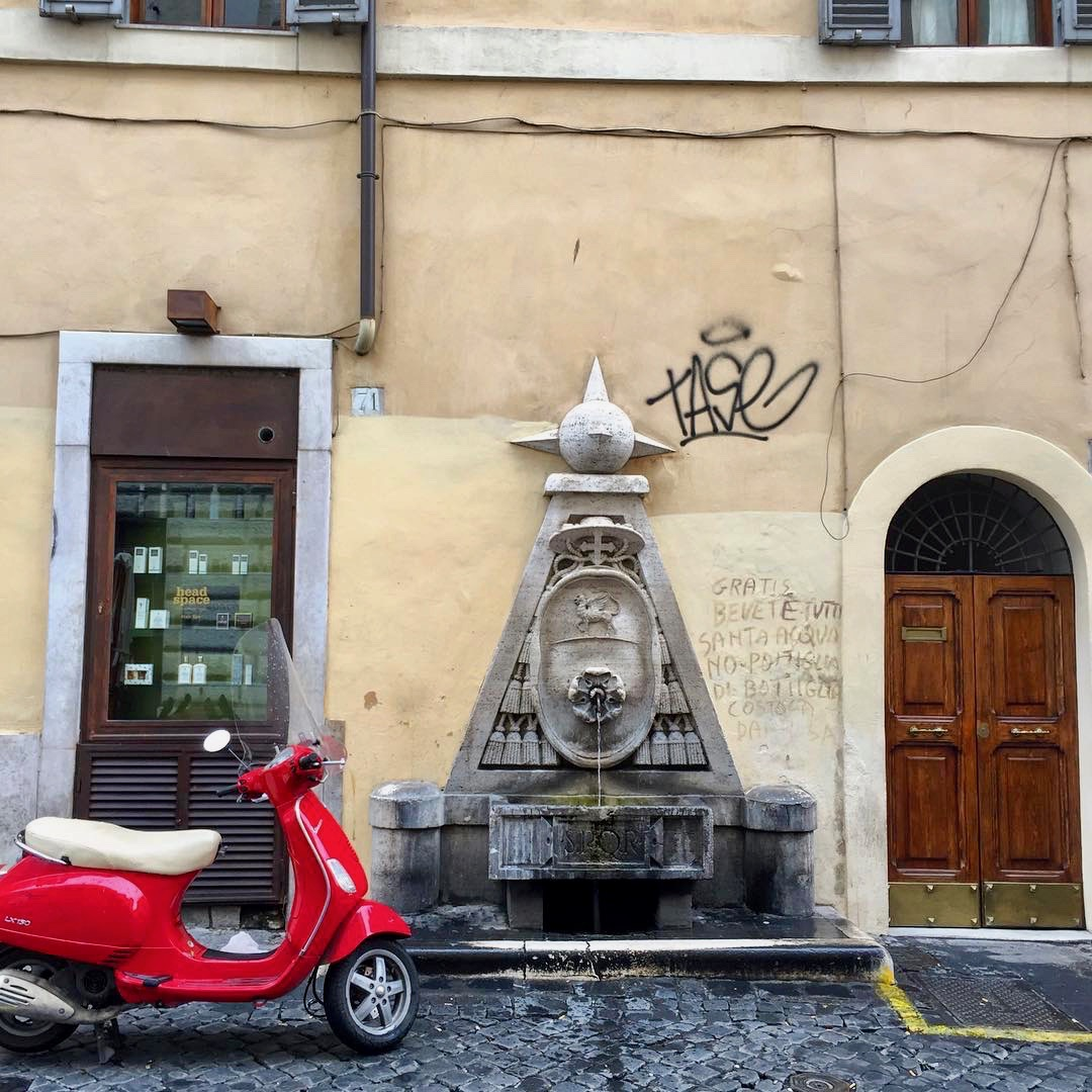 red vespa parked in rome near a fountain